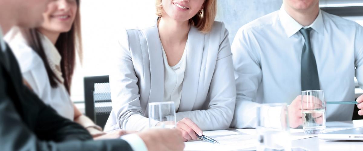 4 Personen am Konferenztisch im geschäftlichen Gespräch