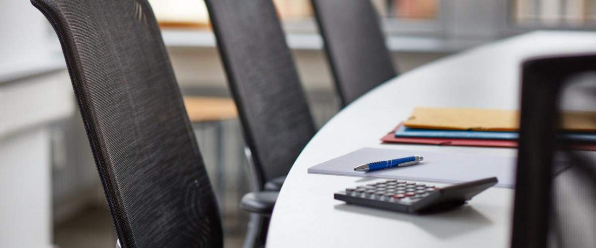 Konferenztisch mit Taschenrechner und Unterlagen