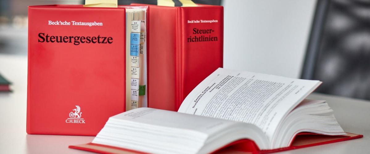 3 rote Gesetzesbücher Verlag C.H. Beck zu Steuergesetzen auf Konferenztisch