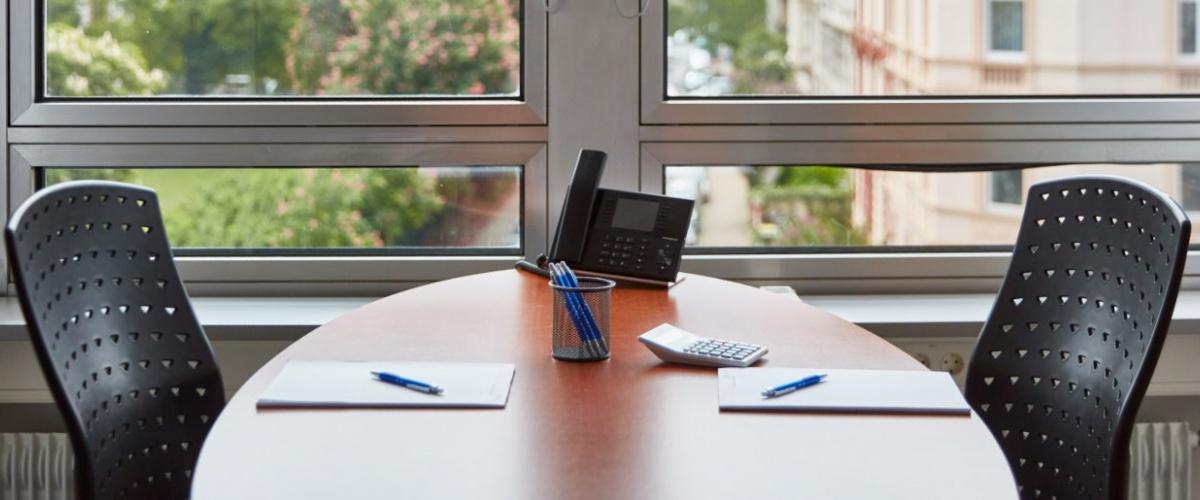 Konferenztisch mit 2 Stühlen, Telefon und Unterlagen mit Blick auf Park und Nachbargebäude