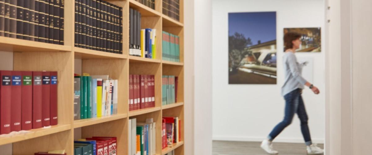 Blick von Bibliothek mit Bücherregal zum Flur, der von Mitarbeiterin durchquert wird